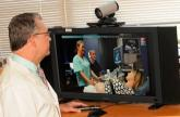 A doctor watches nurse perform an ultrasound via a video screen with a live feed