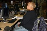 Image: A woman listens intently during a computer basics class