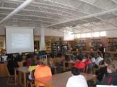 Students in school library view PowerPoint on computer skills