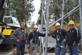 Construction crew members and Dave McGraw pose at the base of a tower