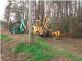 A plowing and trenching crew installs fiber in a wooded area.