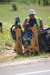 A construction worker uses machinery to dig a hole to run fiber-optic cable