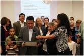 IMG: John Munoz and library members participate in a ribbon-cutting