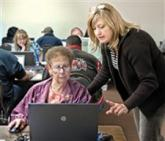 Instructor teaches woman how to use a laptop.
