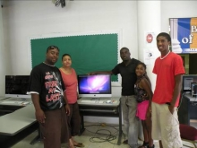 Steve Thigpen and visitors pose in front of the library's new computer