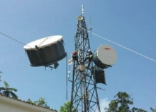 Workers install broadband equipment on a tower in Cayey, Puerto Rico.
