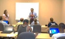 Senator Carper speaks to job seekers sitting at tables with laptops.