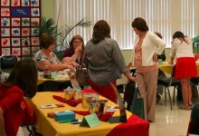 Library patrons walk from table to table at a job fair.