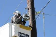 An NTUA crew member begins stringing cable on network poles in New Mexico.