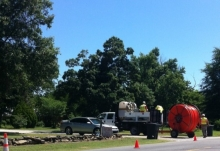 A construction crew stands with equipment and a spool of fiber.