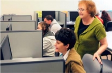 An instructor stands behind a student sitting at a computer workstation.