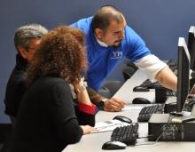 Two students receive e-filing tips from Program Coordinator Ben Delgado