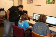 A TDV instructor helps two students navigate the Internet